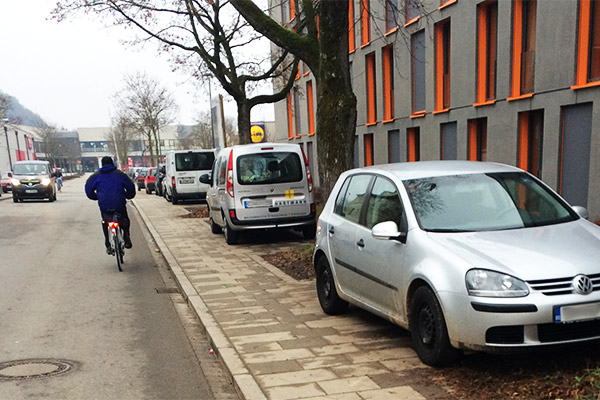 Scharfe Bordsteinkante und Radlfahrer: wenn's eng wird, dennoch Abstand bewahren. Für parkende Autos ein Hindernis.